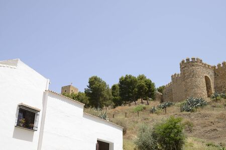 White house with the Moorish fortress in the background  in  Antequera, a city of the province of Malaga, Andalusia, Spain.