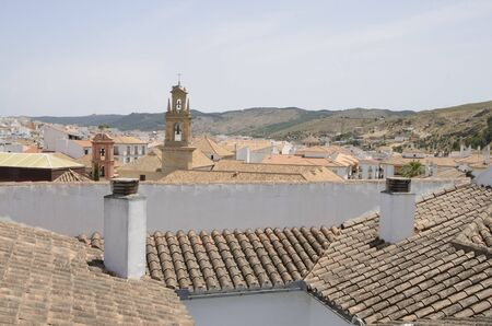 Bell tower among tile roofs in Antequera, a city of the province of Malaga, Andalusia, Spain.