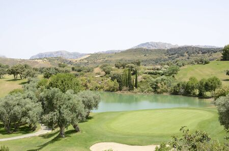 Green lake in golf course located at natural mountain landscape , Andalusia, Spain