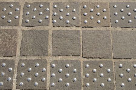 Steel thumbtacks on stone pavement in the old town of Ghent, Belgium.