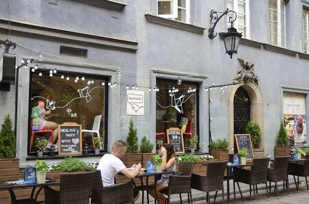 Warsaw, Poland - July 29, 2018: Couple at outdoors bar in the old town of Warsaw, Poland. 新聞圖片