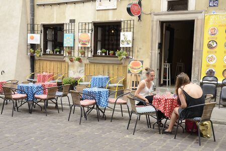 Warsaw, Poland - July 29, 2018: Women having a drink at outdoors bar in the old town of Warsaw, Poland. 新聞圖片