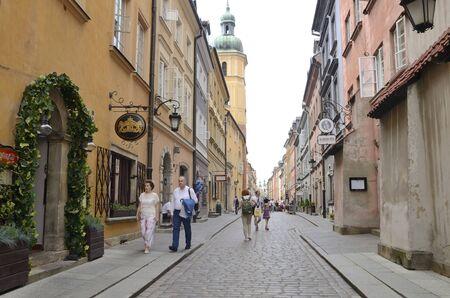 Warsaw, Poland - July 29, 2018: Tourists at cobbled street in the old town of Warsaw, Poland. 新聞圖片