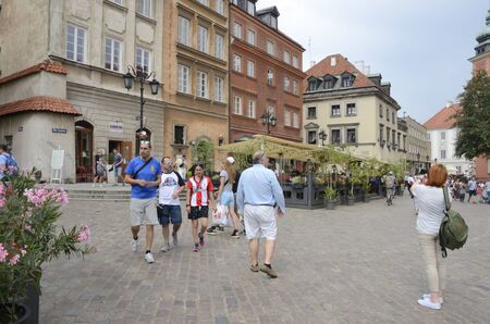 Warsaw, Poland - July 29, 2018: Tourists at cobbled square  in the old town of Warsaw, Poland.