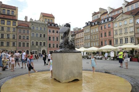 Warsaw, Poland - July 30, 2018:People around the Little Mermaid statue at the Market Square in the old town of Warsaw, Poland.