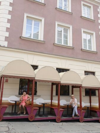 Warsaw, Poland - July 29, 2018: Woman and man in two wagons of outside bar  in the old town of Warsaw, Poland. 新聞圖片