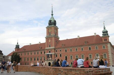 Warsaw, Poland - July 29, 2018: People sitting at brick bench in the famous Square of the castle  in Warsaw, Poland.
