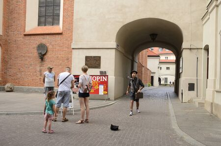 Warsaw, Poland - July 29, 2018: People next to archway  in the old town of Warsaw, Poland.