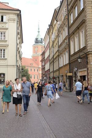 Warsaw, Poland - July 29, 2018: People  walking by  cobbled street in the old town of Warsaw, Poland.
