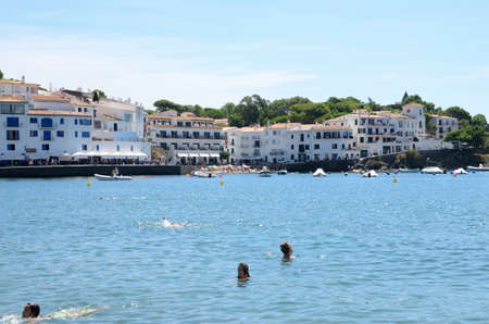 Cadaques, Spain - July 27, 2017: Few people bathing at sea at beach on a summer day in Cadaques, a mediterranean town in the province of Girona, Catalonia, Spain.