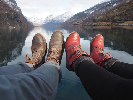 daybreak: Legs of a young couple in love near the lake, Flam, Norway. Stock Photo