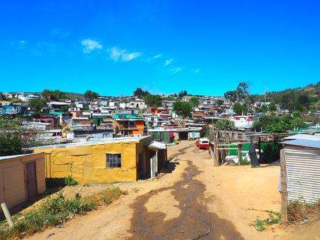 Straat van kleurrijke informele nederzettingen (Sloppenwijk), hutten gemaakt van metaal in de Township of Cape Flats van Stellenbosch, Kaapstad, Zuid-Afrika met blauwe hemel en wolken achtergrond.