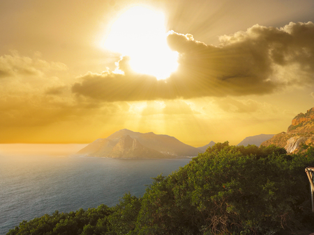 chapmans: Top view from Chapmans Peak Road looking to sea view and mountain in the Atlantic Ocean with gold light sky and clouds background near sunset time, Cape Town, South Africa.