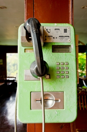Green phone on old wood photo