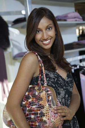 Portrait of young woman with purse at clothes shop Stock Photo - 3540876