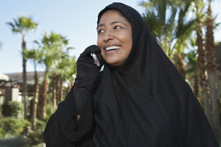 Muslim woman in black hijab talking on mobile, laughing Stock Photo - 3540853