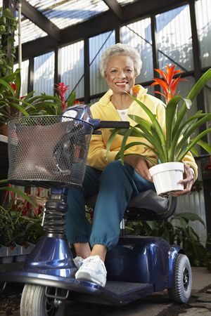 Senior woman on motor scooter in garden center Stock Photo - 3540918