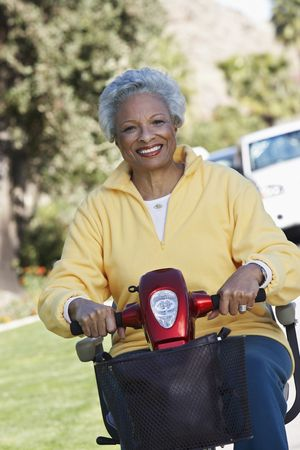 Senior woman on motor scooter on urban street Stock Photo - 3540765