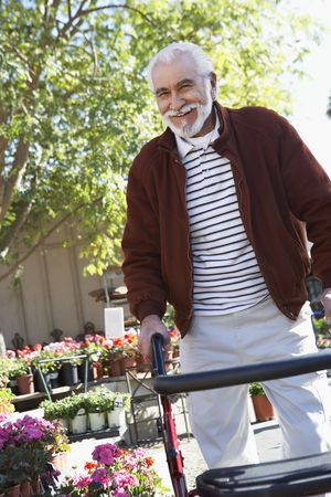 the ageing process: Elderly man with walking frame in garden center LANG_EVOIMAGES