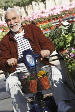 Elderly man on motor scooter in garden center Stock Photo