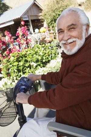 Elderly man on motor scooter Stock Photo