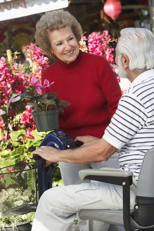 Senior woman talking with elderly man on motor scooter in garden center Stock Photo - 3540932