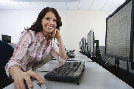 front desk: Woman sitting at desk in front of computer LANG_EVOIMAGES