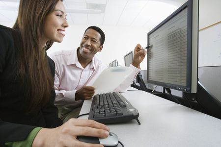 using computer: Man and woman using computer together LANG_EVOIMAGES