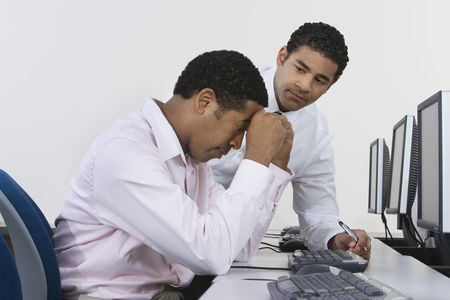 futility: Two business men at desk in front of computer LANG_EVOIMAGES