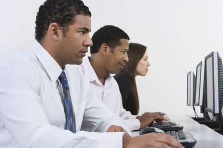 Three business people using computers in office Stock Photo - 3540503