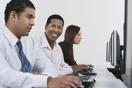 Three business people using computers in office Stock Photo - 3540676