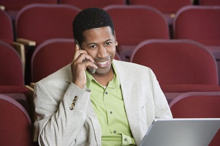 Man sitting in auditorium, using mobile phone and laptop, portrait Stock Photo - 3540913