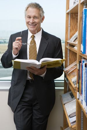 Businessman smiling in library, portrait Stock Photo - 3540844