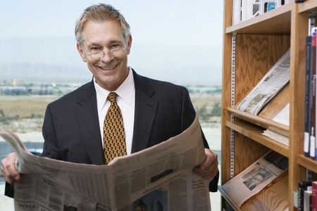Businessman reading newspaper library, portrait Stock Photo - 3540788