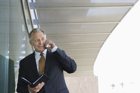 Businessman using cell phone holding day planner Stock Photo - 3540728