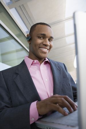 Mid adult man using laptop outdoors, portrait Stock Photo - 3540900