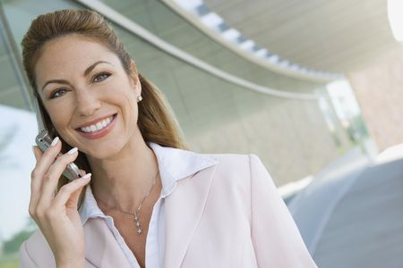 Businesswoman using cell phone on balcony, portrait Reklamní fotografie - 3540688