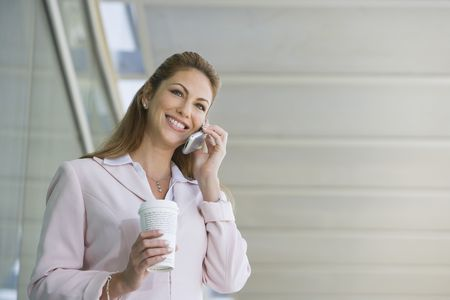 Businesswoman using cell phone with takeout coffee outdoors Stock Photo - 3540684