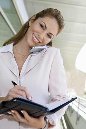 Businesswoman writing in planner while using cell phone outdoors, portrait Stock Photo - 3540751