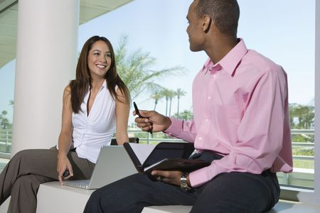 dayplanner: Two business people sitting outdoors with dayplanner and laptop