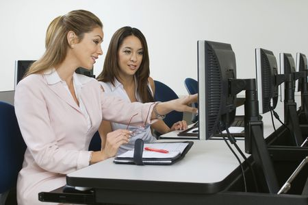 Two business women sitting in computer classroom Stock Photo - 3540678