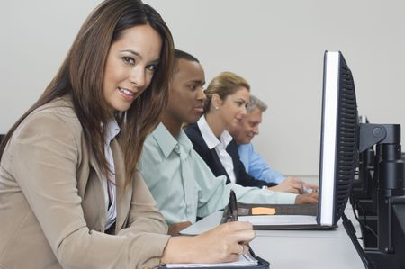 Group of business people using computers in classroom, side view Stock Photo - 3540744