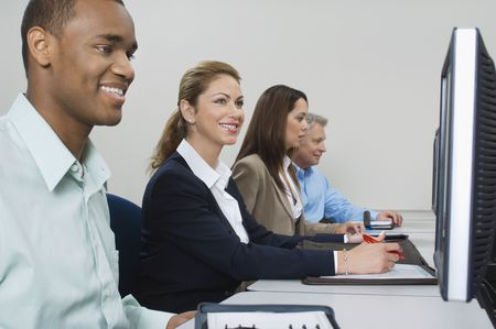 Group of business people using computers in classroom, side view Stock Photo - 3540685