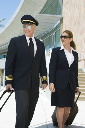 Pilot and flight attendant walking outside building Stock Photo - 3540703