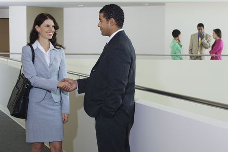 two people with others: Business people shaking hands in office hallway