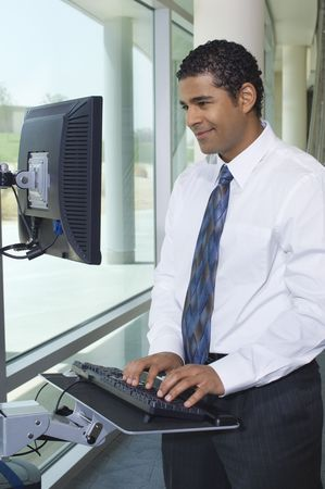 Business man using internet on computer in office hallway Stock Photo - 3540839