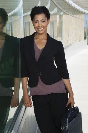 business woman: Business woman with briefcase standing outside office building, portrait