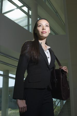 Business woman with handbag standing in office building, low angle view Stock Photo - 3540516