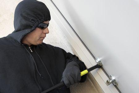 Burglar using crowbar to break into house Stock Photo - 3540494