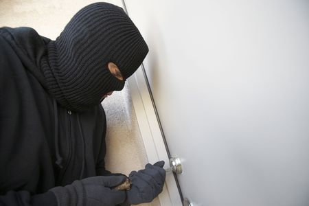 balaclava: Burglar working on lock of front door LANG_EVOIMAGES